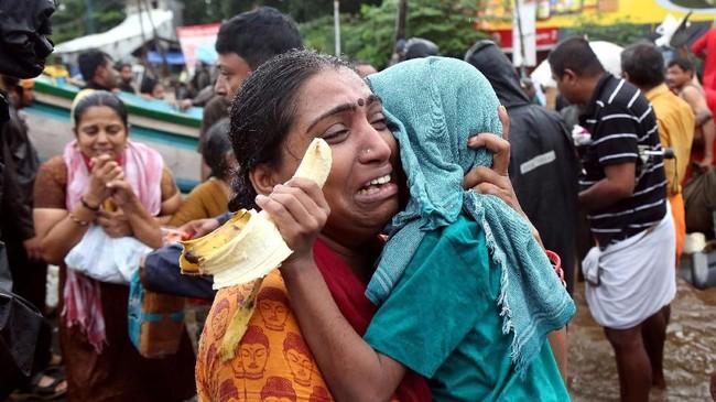 Seorang wanita menangis sambil menggendong putranya saat dievakuasi di Aluva, Kerala, India.