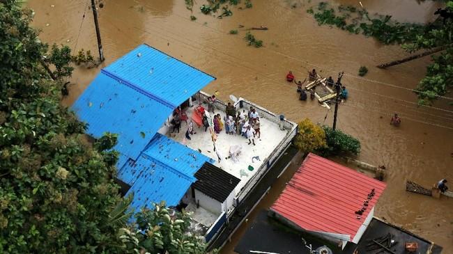 Orang-orang menunggu bantuan di atap-atap rumah mereka di Kerala, India.