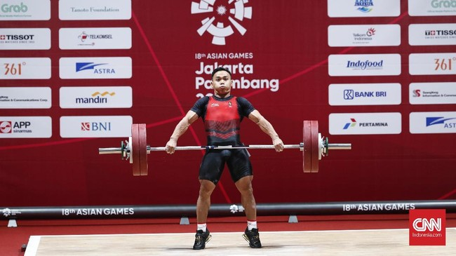 Lifter Indonesia Eko Yuli Irawan melakukan angkatan snatch pada pertandingan angkat besi 62 kilogram. (CNNIndonesia/Safir Makki)