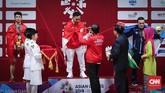 Presiden Joko Widodo mengalungkan medali emas kepada lifter Indonesia Eko Yuli Irawan. Eko Yuli mengalahkan Vietnam Van Vinh Trinh dan lifter Uzbekistan Adkhamjon Ergashev. (CNNIndonesia/Safir Makki)