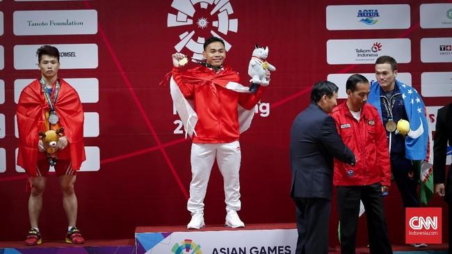 Lifter Indonesia Eko Yuli Irawan memamerkan medali emas 62 kilogram yang direbutnya usai dikalungkan oleh Presiden Joko Widodo. (CNNIndonesia/Safir Makki)