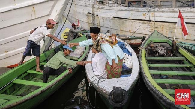 Warga bersiap menaiki sampan usai melaksanakan Sholat Ied Adha 1439 H di pelabuhan Sunda Kelapa, Jakarta, Rabu, 22 Agustus 2018. CNNIndonesia/Adhi Wicaksono.