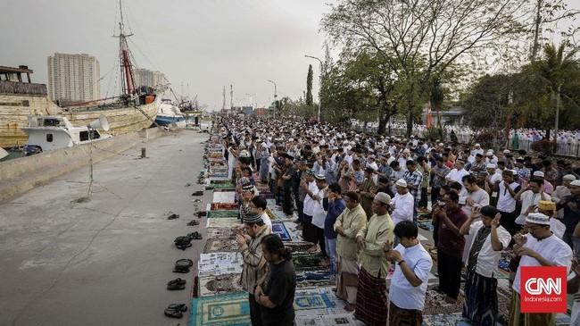 Dengan pemandangan berlatar kapal-kapal di pelabuhan Sunda Kelapa, masyarakat dengan khusuk melaksanakan salat. (CNNIndonesia/Adhi Wicaksono).