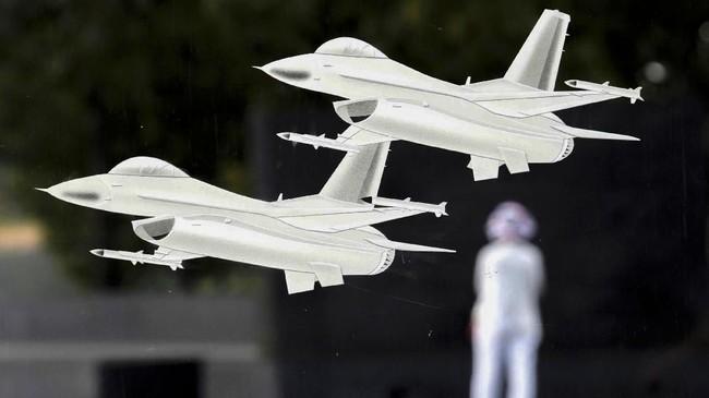Dua miniatur jet F-16 yang ditempel di kaca terlihat seolah terbang melewati seorang pengunjung Museum Angkatan Udara di Arlington, Virgia, AS. (Reuters/Kevin Lamarque)