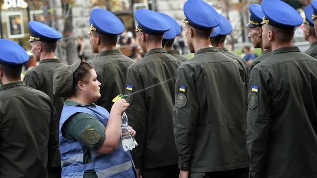 Seorang perawat militer menyemprotkan air untuk mendinginkan tubuh para tentara saat digelarnya latihan pawai Hari Kemerdekaan Ukraina di pusat kota Kiev. (AFP/Sergei Supinsky)