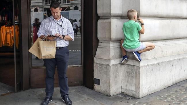 Seorang bocah memanjat tembok luar suatu toko pakaian di jalan Regent, London. (AFP/Daniel Leal-Olivas)