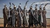 Sekelompok pria dari suku Fulani dari Nigeria menampilkan tarian tradisional untuk menyambut kehadiran PBB di bandara Baradi, Nigeria. PBB mendatangi daerah itu untuk memahami kebutuhan kelompok-kelompok di sana yang terpengaruh perubahan iklim. (AFP/Luis Tato)