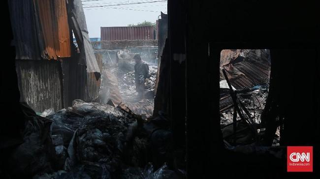Warga mengais benda dan material sisa rumah mereka setelah si jago merah melahap pemukiman kumuh Kampung Walang, Pademangan. Dugaan sementara penyebab kebakaran adalah korsleting listrik dari salah satu rumah warga, Minggu (26/8). (CNN Indonesia/Andry Novelino).