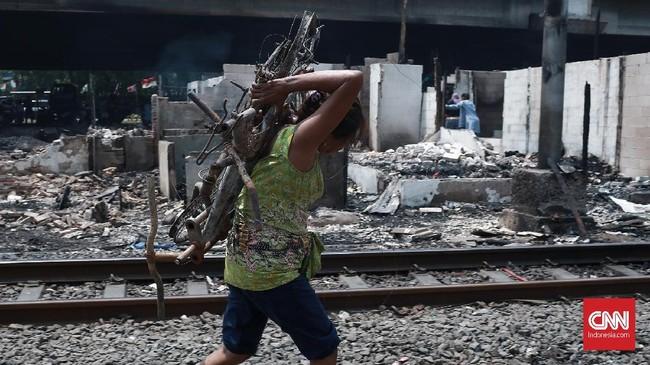 Seorang ibu memikul kerangka motor dan sepeda pasca si jago merah melahap habis harta bendanya. Kebakaran diduga kuat berasal dari percikan api karena korsleting listrikdan mengakibatkan 420 jiwa kehilangan tempat tinggalnya, Jakarta,Minggu, (26/9). (CNN Indonesia/Andry Novelino).
