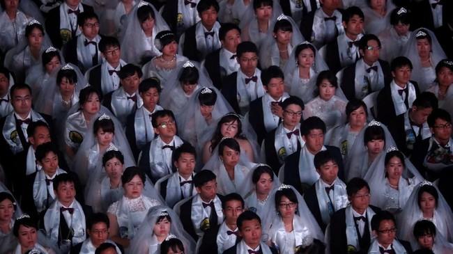 Pernikahan adalah hal yang sakral, tak terkecuali untuk para pasangan di Korea Selatan. Ribuan pasangan Korsel menikah massal di area gereja penyatuan, Gapyeong, Senin (27/8).(REUTERS/Kim Hong-Ji)
