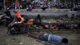 Penggemar Vespa menjadikan motor modifikasi sebagai alas tidur di sela-sela acara. (REUTERS/Darren Whiteside)