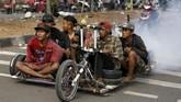 Penggemar Vespa ekstrem menempuh perjalanan jauh dari Semarang menuju Kediri demi menghadiri acara 'Kediri Scooter Festival 2018'. (REUTERS/Darren Whiteside)