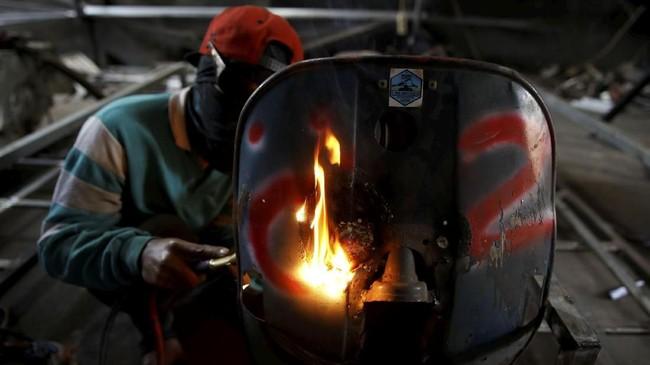 Seorang mekanik tengah memperbaiki Vespa di salah satu bengkel khusus Vespa di Kediri, Jawa Tengah. (REUTERS/Darren Whiteside)