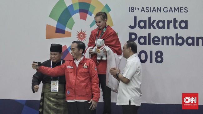 Presiden petahana RI Joko Widodo bersama Prabowo Subianto danatlet pencak silat putri pemenang medali emas, Wewey Wita, di kelas 50-55kg melakukan swafoto bersama. Sementara itu, tampak Ketua Kontingen Indonesia (CdM) di Asian Games 2018, Syafruddin menyaksikan bahagia. (CNNIndonesia/Hesti Rika)