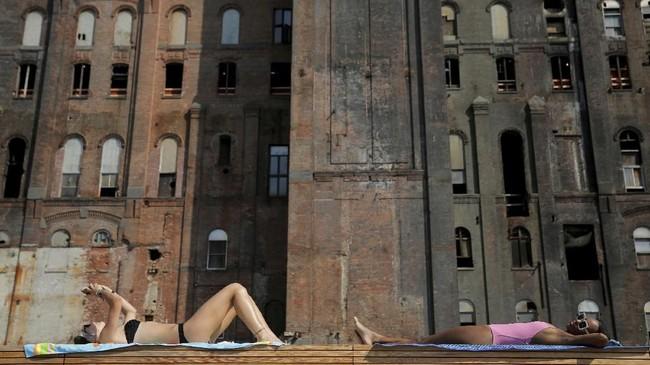 Seorang wanita berjemur di bawah sinar matahari di Taman Domino, Brooklyn, New York. (REUTERS/Andrew Kelly)