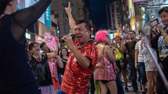 Meski kadang suara dari amplifier dan sorak-sorai serta tepuk tangan membuat sakit kepala, jalanan itu adalah pembudaya kesenian lokal. (AFP PHOTO / Philip FONG)