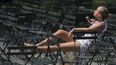 Seorang wanita terlihat bersantai di Taman Bryant Park, Manhattan, New York. (REUTERS/Andrew Kelly)
