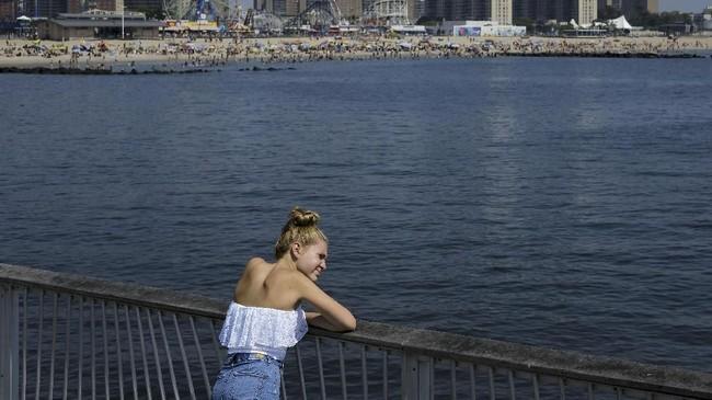 Seorang wanita berdiri di pesisir Coney Island Beach untuk menikmati angin yang berembus di tengah udara New York yang gerah. (Drew Angerer/Getty Images/AFP)
