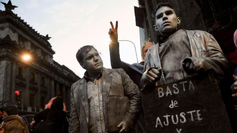 Para pendemo yang mengecat tubuhnya membawa poster bertuliskan