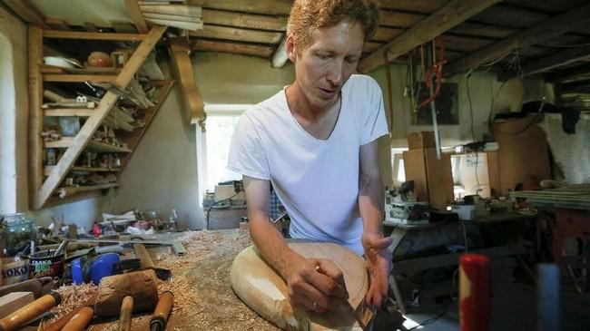 Fedynsky saat mengerjakan pembuatan alat musik tradisional Ukraina di bengkelnya.