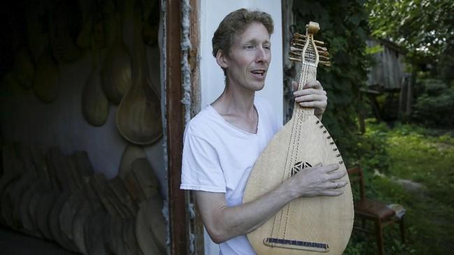 Musisi Yuriy Fedynsky memainkan alat musik petik asal Ukraina bernama kobza di rumah sekaligus bengkel pembuatan alat musiknya, Desa Kryachkivka, Ukraina.