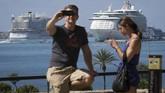 Sepasang turis berfoto di pinggir pelabuhan Palma de Mallorca. (AFP PHOTO/Jaime Reina)