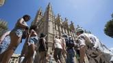 Antrean turis di Katedral Palma de Mallorca, di Spanyol. Spanyol didatangi 89 juta turis mancanegara setiap tahunnya. Posisinya kini tepat di bawah Perancis sebagai destinasi wisata favorit. Sebagian besar turis datang ke Kepulauan Palma de Mallorca. (AFP PHOTO/Jaime Reina)