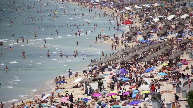 Turis terlihat mengerumuni Pantai El Arenal di Mallorca, Spanyol.(REUTERS/Enrique Calvo)