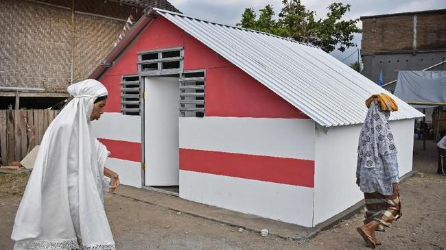 Sejumlah warga melintas di dekat bangunan Rumah Hunian Sementara yang dibangun BUMN di Posko Pengungsian Desa Kekait, Kecamatan Gunungsari, Lombok Barat, NTB, Senin (27/8). (ANTARA FOTO/Ahmad Subaidi)