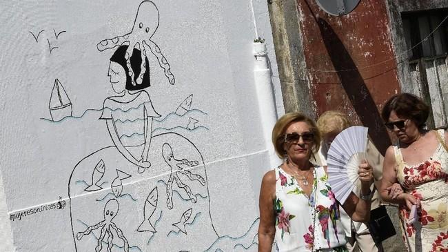 Pada 2008, seorang seniman bernama Eduardo Hermida frustasi melihat kawasan tempat tinggalnya di Canido nyaris mati karena ditinggal penduduknya. Ia meluapkan perasaannya itu melalui sebuah lukisan mural di dinding rumah tak bertuan. (AFP PHOTO / MIGUEL RIOPA)