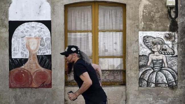 Untuk merapikan karya para seniman yang terus muncul, diadakan sebuah festival menggambar mural di dinding bangunan kawasan tersebut setiap tahunnya dan diberi nama Festival Art Meninas de Canido. (AFP PHOTO / MIGUEL RIOPA)