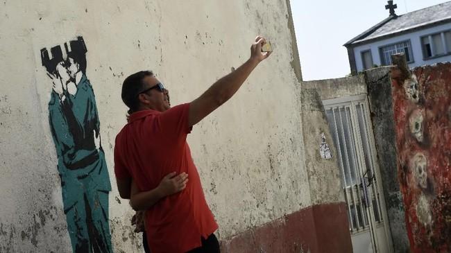 Bahkan, seniman mural legendaris Bansky disebut sempat memberikan kontribusi dalam dinding di kawasan ini. Namun Bansky membantah bahwa karya penjaga berciuman seperti di gambar ini adalah miliknya. (AFP PHOTO / MIGUEL RIOPA)