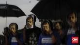 Para peserta Kamisan memasang topeng Munir di depan paras mereka. Munir tewas dalam penerbangan dari Indonesia menuju Belanda pada 7 September 2004.(CNN Indonesia/Adhi Wicaksono)