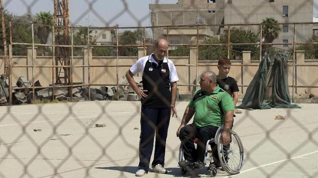PelatihTamer Ghanemsedang berbincang denganThaer al-Ali dalam sebuah sesi latihan. Mereka bersiap untuk kembali menekuni olahraga angkat berat. (AFP PHOTO / Zaid AL-OBEIDI)