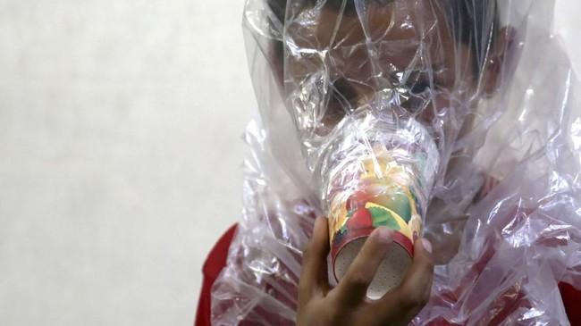 Tak mau kepanikan itu terulang, mereka bersiap. Seorang ayah terlihat menempelkan gelas kertas warna-warni berisi kapas dan arang ke wajah anaknya, kemudian membungkus kepala bocah itu dengan kantung plastik. (Reuters/Khalil Ashawi)