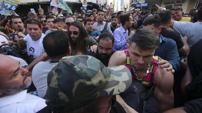 Bolsonaro tampak kesakitan saat ditusuk dan jatuh ke pelukan orang-orang yang ada di sekitarnya saat kampanye. (Felipe Couri / Minas Tribune / via REUTERS)