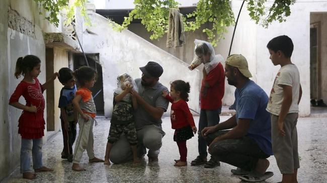 Ia kemudian tersenyum menatap anaknya yang kini sudah siap menghadapi segala kemungkinan keracunan zat kimia ketika pertempuran antara pasukan pemerintah dan pemberontak memanas. (Reuters/Khalil Ashawi)