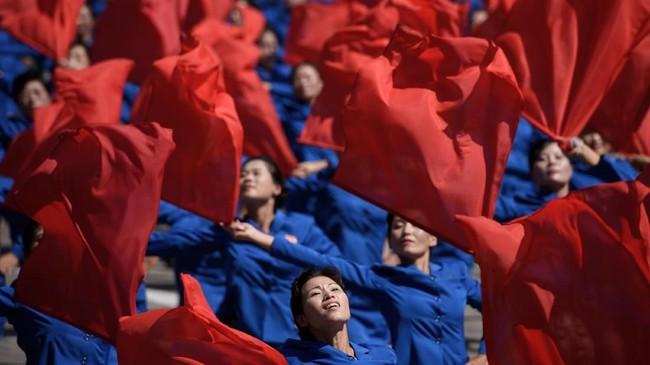 Para peserta parade yang melambaikan bendera dalam gelaran selebrasi hari jadi ke-70 Korea Utara. (AFP PHOTO / Ed JONES)