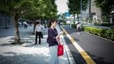 Seorang wanita melihat teleponnya di sepanjang jalan di Tokyo. (AFP PHOTO / Martin BUREAU)