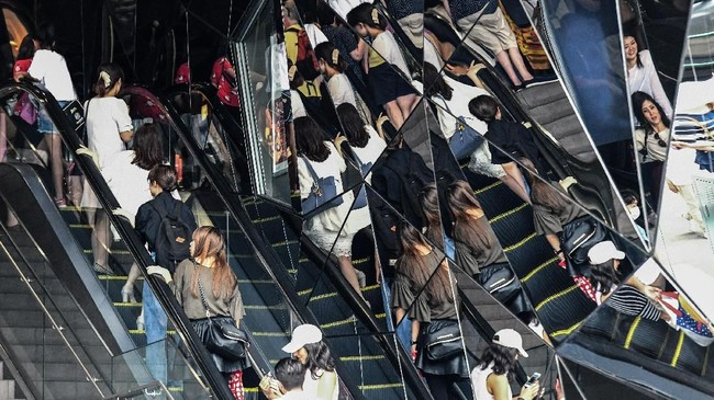 Pembeli tercermin pada cermin dinding di gerbang pusat perbelanjaan Omotesando. (AFP PHOTO / Toshifumi KITAMURA)