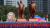 Orang-orang membawa bendera di depan patung pendiri Korea Utara Kim Il Sung (Kiri) dan mendiang pemimpin Kim Jong Il selama parade militer menandai peringatan 70 tahun pendirian Korea Utara di Pyongyang. (REUTERS/Danish Siddiqui)