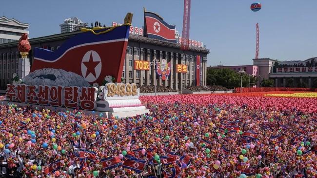 Para peserta melambai-lambaikan bunga saat mereka berbaris melewati sebuah balkon dari mana pemimpin Korea Utara Kim Jong Un sedang menonton di Lapangan Kim Il Sung di Pyongyang. (AFP PHOTO/Ed JONES)