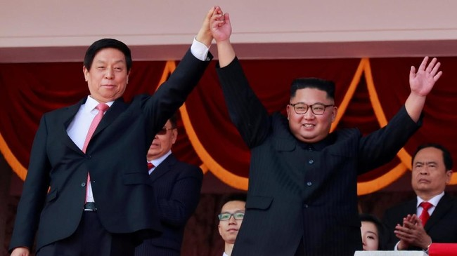 Pemimpin Korea Utara Kim Jong Un dan Ketua Komite Tetap Kongres Rakyat Nasional (NPC) Li Zhanshu melambaikan tangan kepada orang-orang saat menghadiri parade militer menandai peringatan 70 tahun pendirian Korea Utara. (REUTERS/Danish Siddiqui)