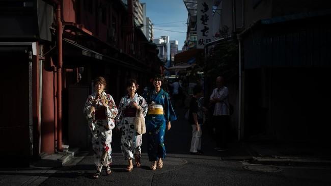 Wanita yang mengenakan kimono berjalan di sepanjang jalan di distrik Asakusa, Tokyo. (AFP PHOTO / Martin BUREAU)