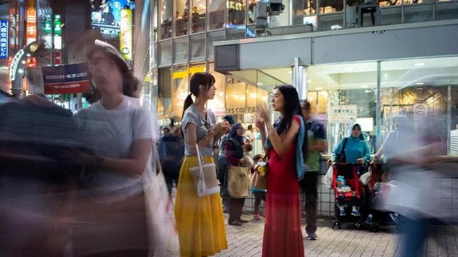 Dua wanita sedang berbincang di depan stasiun di Tokyo. (AFP PHOTO / Martin BUREAU)