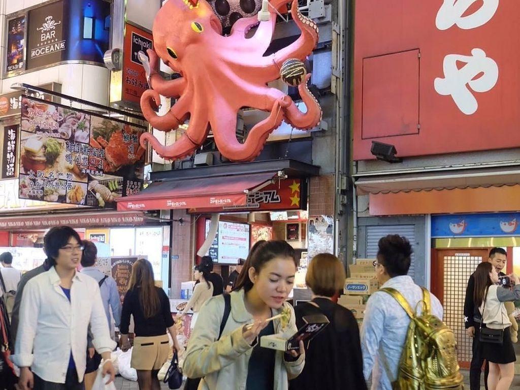 Begini nih gayanya saat melahap sajian berbahan dasar gurita di Jepang. Saking semangat nya makan, tulis Riri saat mengunggah foto makan sambil berdiri di depan outletnya langsung. Foto: Instagram rianarizki