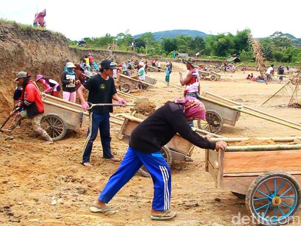 Dengan menggunakan gerobak kayu ratusan warga mengais rezeki mengerjakan penimbunan untuk perpanjangan landasan pacu.