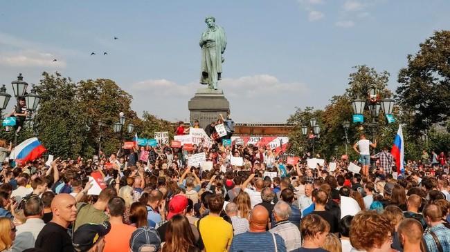 Aksi protes ini digagas oleh pihak oposisi pemerintah yaitu Alexander Navalny yang kini ditahan pemerintah Rusia. Dalam foto terlihat para demonstran menyuarakan sikap mereka di dekat patung sastrawan Rusia, Alexander Pushkin, di Moskow. (REUTERS/Grigory Dukor)