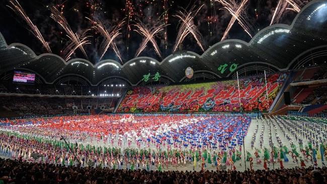 Formasi drone berdesing membentuk berbagai tulisan, sementara video pertemuan bersejarah Kim Jong-un dan Presiden Korea Selatan, Moon Jae-in, pada pertengahan tahun ini diputar di layar lebar. (AFP Photo/Ed Jones)