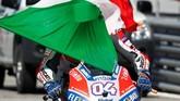 Andrea Dovizioso yang terselimuti bendera Italia. Ia begitu bangga untuk kali pertama menang di MotoGP San Marino. (REUTERS/Max Rossi TPX IMAGES OF THE DAY)